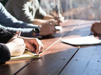Menschen mit Notizblöcken sitzen an einem sonnigen Holztisch