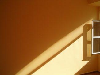 Ein Fenster wirft einen Schatten auf die Wand